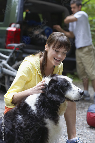 Woman with dog outdoors, man loading car in background