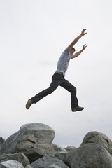 Man leaping with arms raised over rock