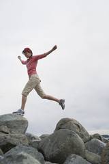 Woman with arms outstretched, jumping on rocks