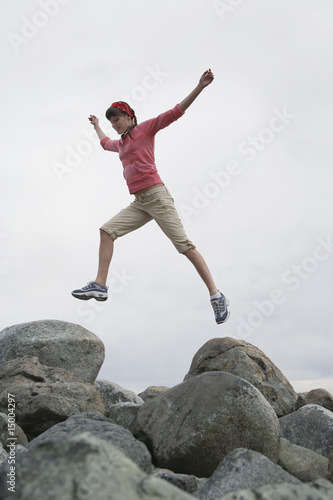 Woman leaping with arms raised over rocks