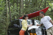 Couple with map on car bonnet in forest