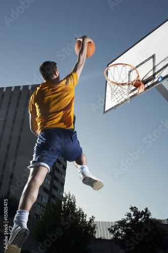 Young man with basketball jumping towards hoop, mid-air