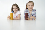 Two girls 7-9 sitting at table with orange and chocolate drinks, portrait