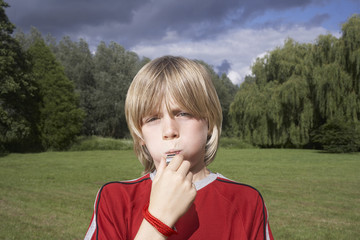 Portrait of boy 7-9 blowing whistle in meadow