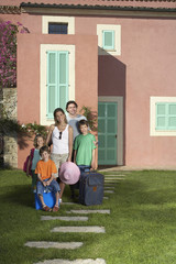 Portrait of family with three children 6-11 with luggage in front of house