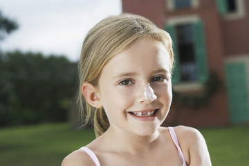 Portrait of girl 5-6 with sunscreen on nose