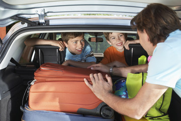 Father talking to boys 6-11 sitting in loaded car