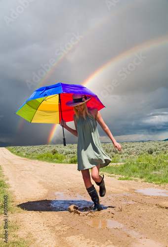 Girl with a rainbow umbrella splashing water in a puddle