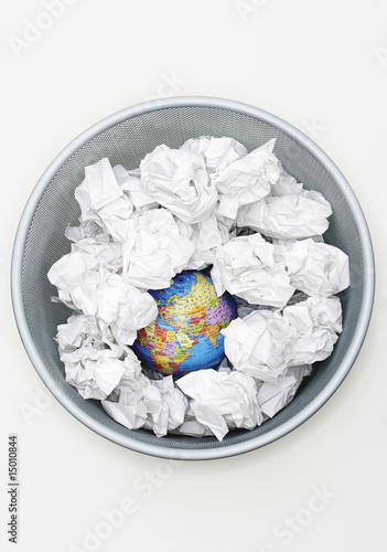 Waste bin with globe among crumpled papers, view from above
