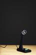 Old fashioned microphone on desk, black background