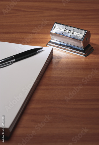 Notepad, pen and old fashioned calendar in desk