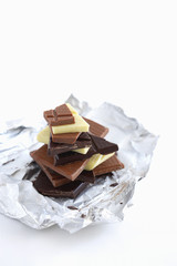 Stack of different chocolate pieces on aluminum foil,  studio shot