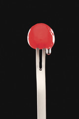 Single cocktail cherry in fork, black background