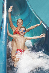 Brother and sister 7-12 with arms outstretched, on water slide