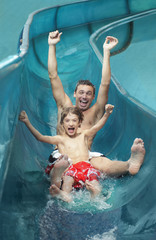 Father and son 7-9 with arms outstretched, on water slide