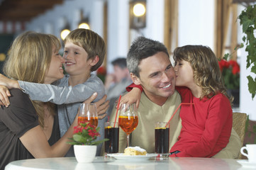 Parents and children 7-9 with drinks, embracing at restaurant