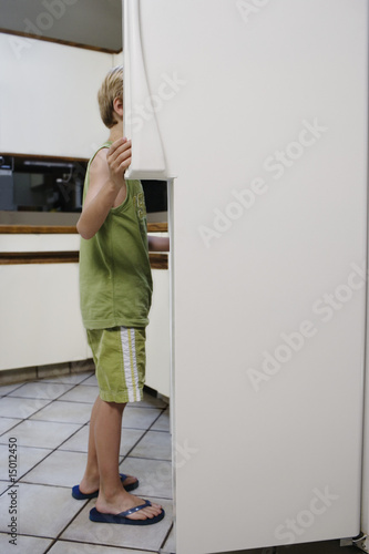 Boy 5-6 looking into fridge