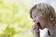 Boy 10-12 eating apple, profile
