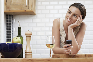 Young woman holding mobile phone, leaning on kitchen counter