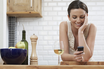 Young woman text messaging, leaning on kitchen counter