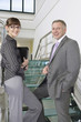 Business man and woman on stairs in office building, portrait