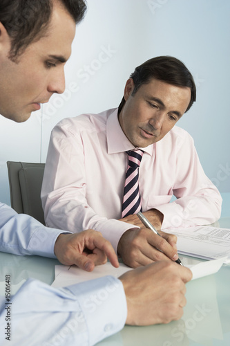 Two business men working at table in office