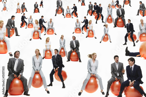 Large group of business people bouncing on inflatable balls, studio shot