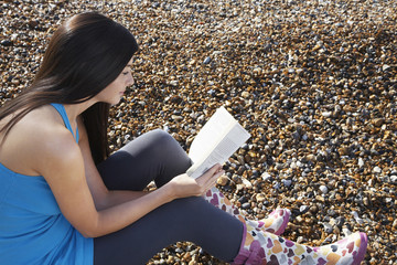 Young woman sitting on beach reading book, side view