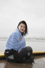 Female surfer sitting in shallow water covered with towel