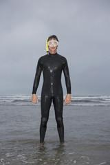 Man in wetsuit wearing snorkle, standing in water on beach, portrait