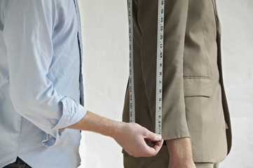 Tailor measuring jacket sleeve on man, side view, close up, mid section