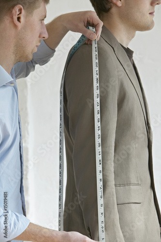 Tailor measuring jacket sleeve on man, side view, close up