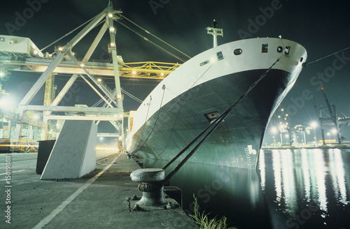 Containership being loaded in dock at night