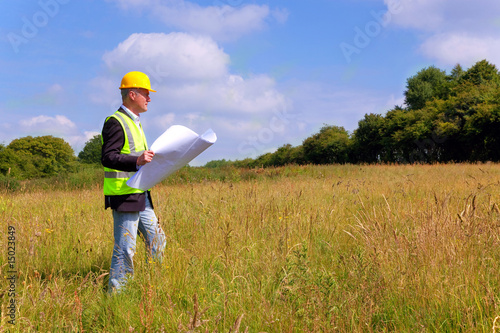 Architect surveying a new building plot - 15023849