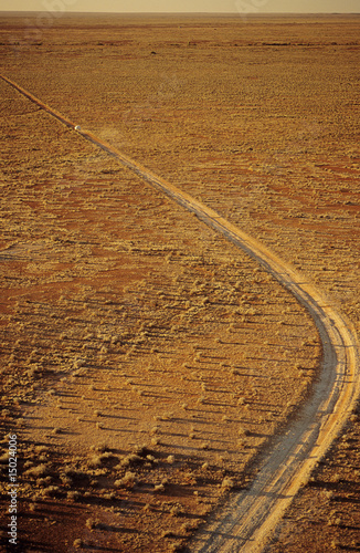 Car driving along desert road, outback Australia