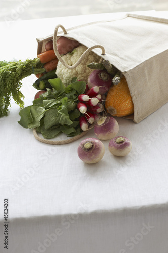 Bag full of fresh vegetables on table, close-up