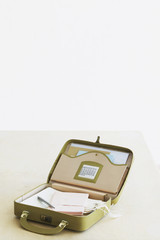 Suitcase with stationery items, elevated view, studio shot
