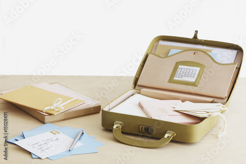 Postcard and envelopes next to suitcase with stationery items, elevated view, studio shot