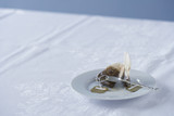 Used tea bag on saucer on table