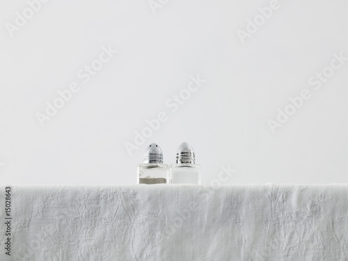 Salt and pepper shakers on table, low angle view, studio shot