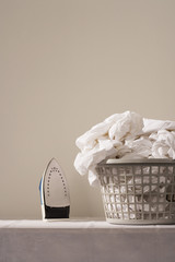 Iron next to laundry basket on table