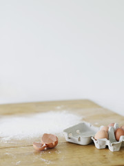 Eggs and flour scattered on table top