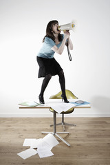 Woman standing on desk, shouting through megaphone
