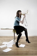 Woman sitting on desk, shouting through megaphone