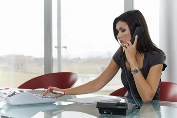 Professional woman on telephone using calculator