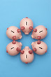 Piggy banks on blue background, view from above