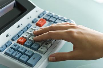 Closeup of woman's hand using calculator