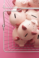 Shopping cart with piggy banks on pink background, view from above