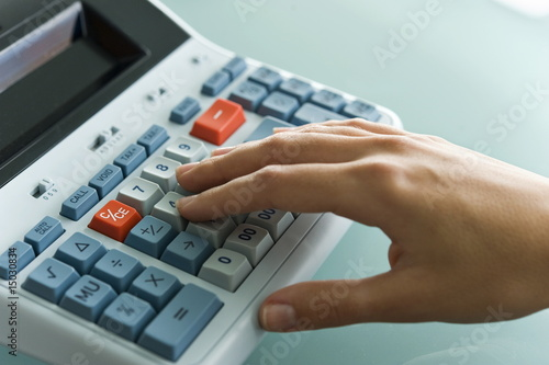 Closeup of woman's hand using calculator