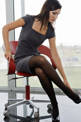 Professional woman sitting on office chair adjusting her heel